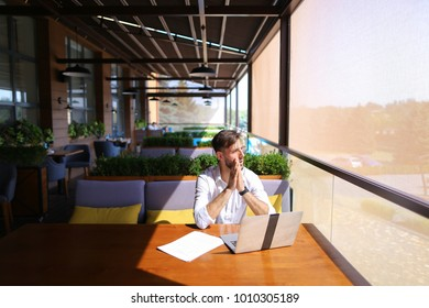 Inventory strategist solving problems and using laptop at cafe table. Clever hardworking man dressed in white shirt working with papers. Concept of  analyzing model forecast  to design contingency pla