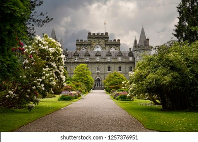 Inveraray, Scotland, UK - June 8, 2018: Turreted Inveraray Castle in Gothic Revival style from the flower gardens with dark clouds in the Scottish Highlands Scotland UK