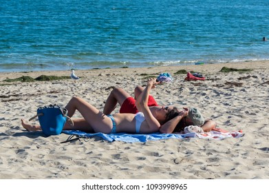 Inverloch, Australia - January 27, 2018: young couple lying on Inverloch beach, a popular seaside holiday town in South Gippsland.