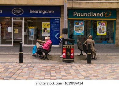 INVERNESS, Scotland, UK - July 5, 2017: Shoppers taking a break in Eastgate in central Inverness, Scotland, UK with a Boots chemist and Poundland shop in the background