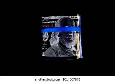 Inverse photo of us money rolled up with a rubber band isolated on white. the most popular money.