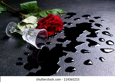 The inverted glass of wine  and red rose