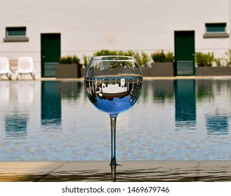 An inverted image of a white pavilion seen in a wine glass perched on the edge of a swimming pool of calm water.