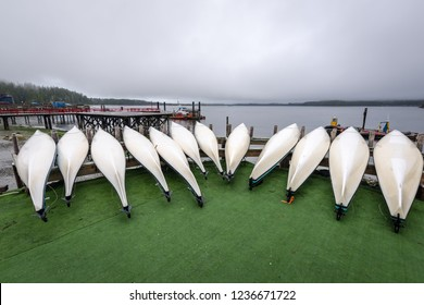 inverted kayaks lined up side by side on a dock in the tourist town of Tofino waiting to be rented out to paddle around the small islands of Clayoquot Sound, Vancouver Island, British Columbia, Canada