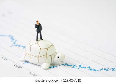 Invest with slow but steady for long term success metaphor, miniature people businessman riding turtle or tortoise walking on rising growth stock market value graph, value investment concept.