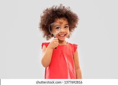 investigation, discovery and vision concept - happy little african american girl looking through magnifying glass over grey background