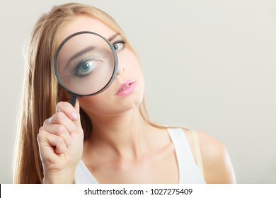 Investigation exploration education concept. Closeup woman face, girl holding on eye magnifying glass loupe