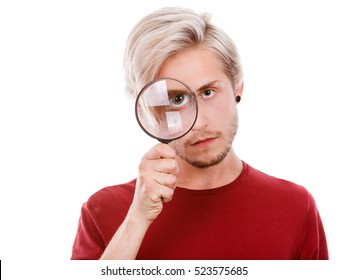 Investigation exploration education concept. Young guy holding on eye magnifying glass looking through loupe, isolated on white