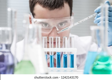 Investigator checking test tubes. Man wears protective goggles