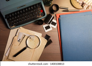 Investigator desk with confidential documents, vintage typewriter, film, magnifying glass and hat. Secret documents investigation concept.