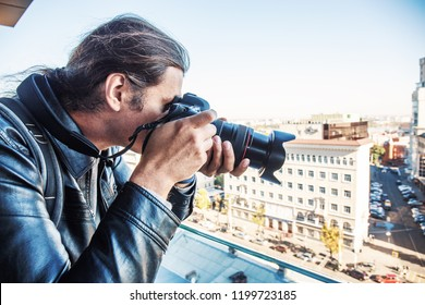 Investigator or private detective or reporter or paparazzi taking photo from balcony of a tall building with professional camera
