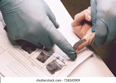The investigator takes fingerprints from the suspect in the crime. Investigation is a crime. Crime.