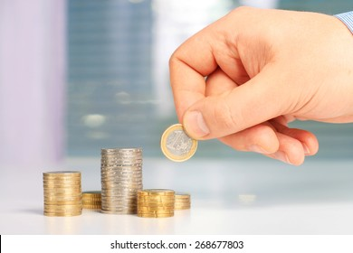 Investing concept. Hand putting euro coin on stack of coins