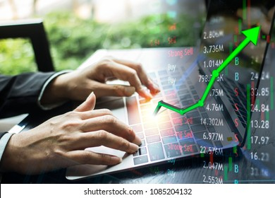Investing with laptop online.  Stock market concept gain and profits with faded candlestick charts.