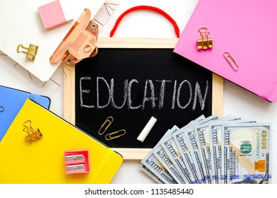 Investing money in expensive education, college tuition & fees concept. Pack of new one hundred dollar bills, notebooks, school supplies, black chalk board.