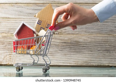 Investing in real estate properties with shopping trolley with miniature houses