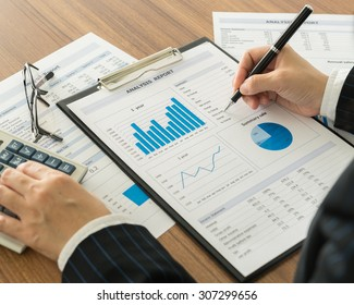 Investment adviser are analyzing the data from business chart and graph.