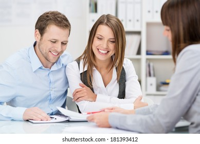 Investment adviser giving a presentation to a friendly smiling young couple seated at her desk in the office