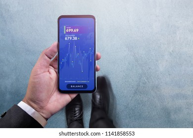 Investment and Analysis concept. Top View of Businessman Walking and holding Smartphone with Chart of Financial Stock Marketing on Screen