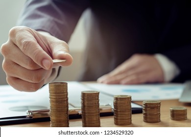 investment concept, businessman counting on lot of coin in modern office