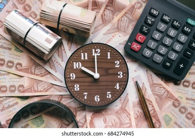 Investment and economy concept, wood clock, roll of banknote, calculator, pen and magnifying glass on thousand  money currency background