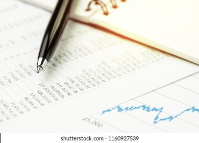 Investment market price list, stocks, bonds or asset value analysis concept, pen on note book with graph and chart, price numbers table report on table with golden flare light.