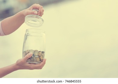 Investment, retirement, taxes and passive income concept. Coins in a glass jar in hand, blur focus. Instagram toned on photo