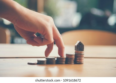Investment Saving Money Concept. Woman hand go up on budget to buy house real estate agent. Gold coins stack symbol buy property mortgage money loan with stack of money coin