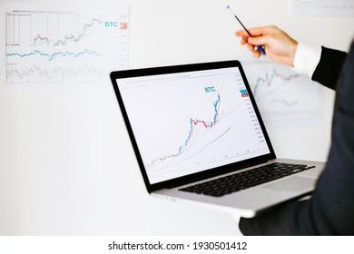 investment stockbroker price trend analysis. Stock market trader analyzing bitcoin price trend. Investment broker trading bitcoin crypto currency using phone and laptop.