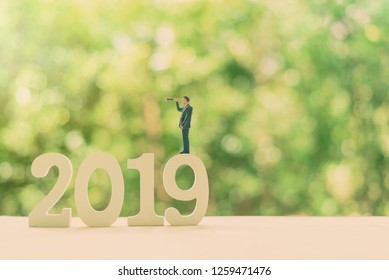 Investment vision, asset management strategy for future growth, financial concept : CEO or CFO businessman with a monocular telescope or spyglass stands on number 2019, sees /seeks for new opportunity