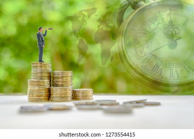 Investment vision, asset management strategy for future growth, financial concept : Businessman with a monocular telescope or spyglass stands on money coins, sees /seeks for new long term opportunity