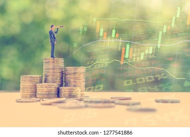 Investment vision, asset management strategy for future growth, financial concept : Businessman with monocular telescope or spyglass stands on money coins, search / look for new long term opportunity