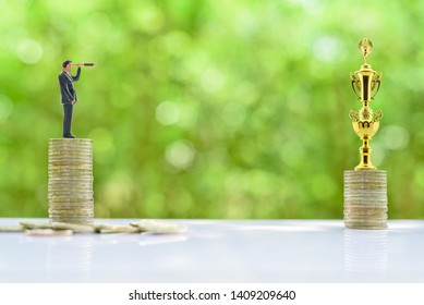 Investment vision, asset management strategy for future growth, financial concept : Businessman with a monocular telescope or spyglass stands on money coins, sees /seeks for new long-term opportunity