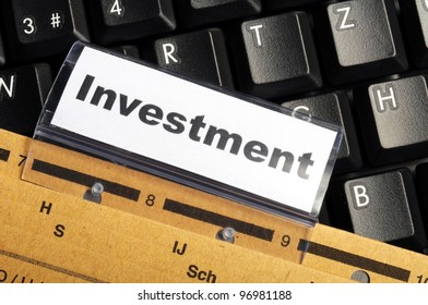 investment word on business folder showing financial success concept
