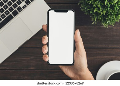 Investor analyzing stock market investments with on blank smartphone screen, copy space