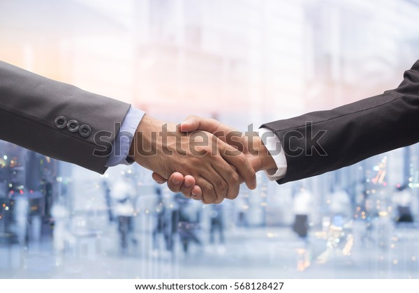 investor businessman in suit handshake together for successful on double exposure night city and walking people background,executive meeting concept