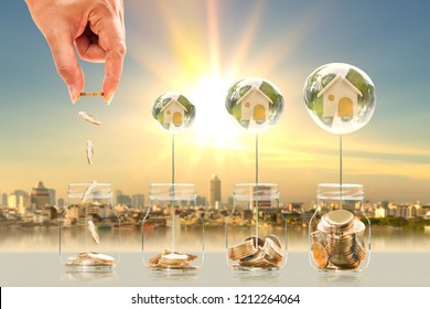 Investor hand drop a coin in the bottle and home in crystal bubble with saving money on photo blur cityscape on sunlight background, business investment and dream as buy house and real estate concept.