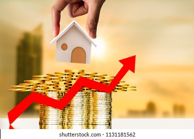 Investor hand hold a home model put on the stacked coin and red arrow graph with growing value on photo blur cityscape background, financial of real estate business investment and fund concept.