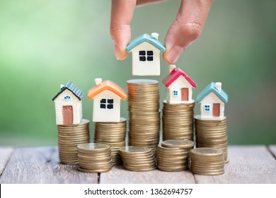 Investor show hand holding a model home and coin , Saving money for buy a new house and loan for plan business investment for real estate in the future concept.