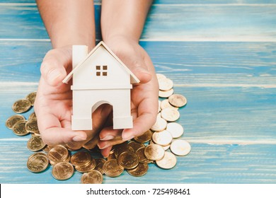 Investor show hand holding a model home on a coin and the wooden vintage background, Saving money for buy a new house and loan for plan business investment for real estate in the future concept.