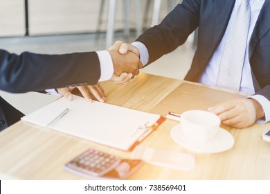 Investors reassure businessman or foreign partners in real estate investment new project. Lawyers join hands with clients to agree on the job with confidence while checking documents at coffee shop.