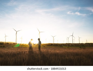 Investors and technician who are out of focus in the foreground are standing in talks about wind turbine power generation, Wind turbine farm is an alternative electricity source for business.