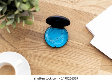 Invisalign braces in blue package laying on wooden table