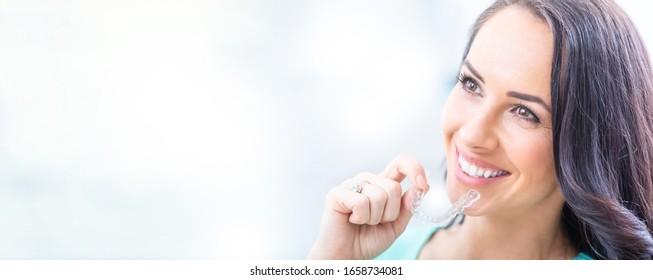 Invisalign Kieferorthopädie Konzept - Junge attraktive Frauen, die halten - mit unsichtbaren Brühen oder Trainer.