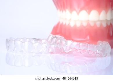 Invisible aligners plastic braces dentistry retainers to straighten teeth; temporary removable straightener with plastic dentures on white background