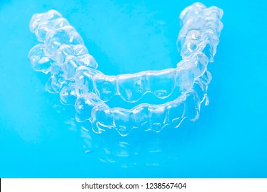 Invisible dental teeth brackets tooth aligners on blue background, plastic braces dentistry retainers to straighten teeth. Orthodontic temporary removable straighteners in dentist office dental