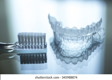 Invisible dental teeth brackets tooth aligners plastic braces retainers to straighten teeth and toothbrush dental hygien care. Orthodontic temporary removable straighteners