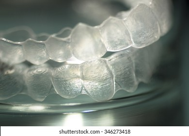 Invisible Invisalign plastic dental teeth brackets tooth braces isolated with shallow depth of focus artistic photograph.