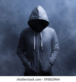 invisible man in the hood.On blue background in smoke