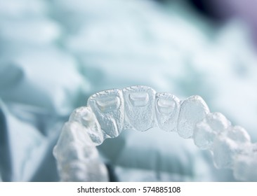 Invisible orthodontics cosmetic brackets tooth aligners plastic braces modern teeth retainers isolated closeup.